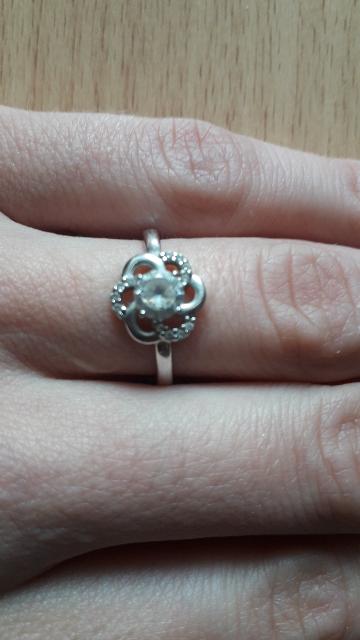 Кольцо в виде цветка с крупным камнем в центре и мелкими на лепестках.