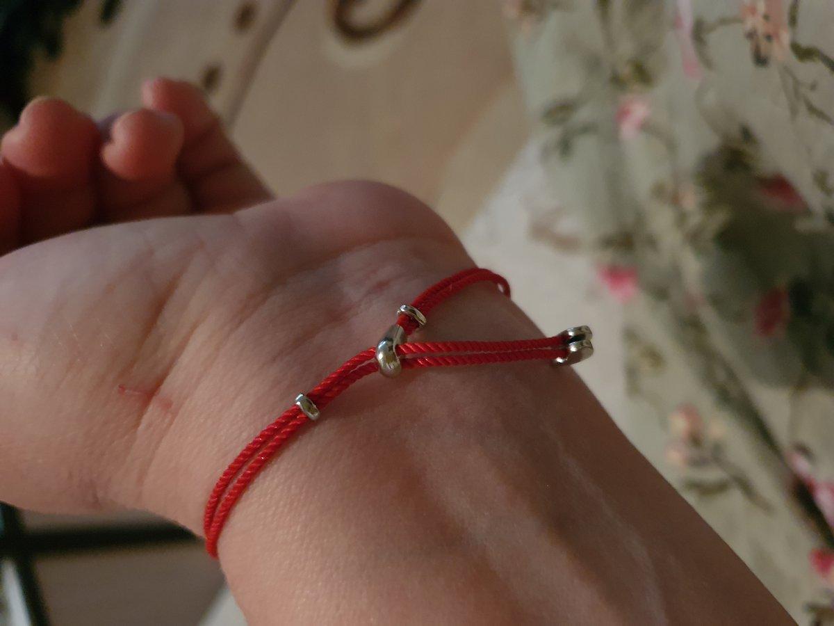 Серебряное сердце на красном шнурке.